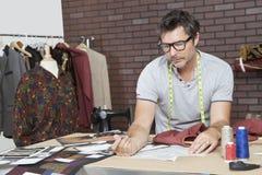 Reifer männlicher Modedesigner, der im Entwurfsstudio arbeitet stockfotografie