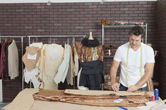 Reifer männlicher Modedesigner, der im Entwurfsstudio arbeitet stockfotos