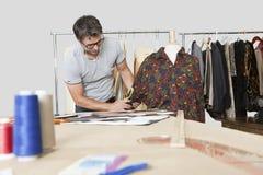 Reifer männlicher Modedesigner, der Maß des Hemdes im Entwurfsstudio nimmt stockbilder