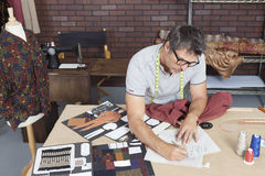 Reifer männlicher Modedesigner, der an Skizze im Entwurfsstudio arbeitet stockfoto