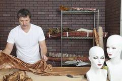 Reifer männlicher Modedesigner, der an Stoff im Designstudio arbeitet lizenzfreies stockfoto
