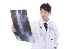 Reifer männlicher Radiologe Asiens, der den Röntgenstrahl des Patienten studiert Stockfotografie