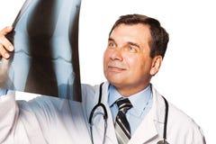 Reifer männlicher Radiologe, der den Röntgenstrahl des Patienten studiert Stockfotos
