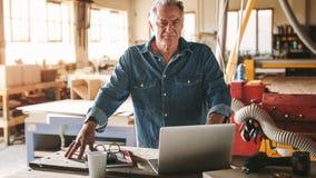 Reifer männlicher Tischler in seiner Werkstatt stockbild