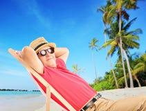 Reifer männlicher Tourist, der auf einem Strand nahe bei einem Meer genießt Stockfotografie