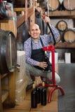 Reifer männlicher Weinhersteller, der Flasche Wein bekorkt lizenzfreie stockbilder