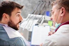Reifer männlicher Zahnarzt, der die Sonderkommandos des Patienten auf ein Klemmbrett, beraten während der Prüfung in der zahnmedi lizenzfreie stockfotografie