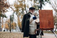 Reifer Maler, der Landschaftsbild im Park schafft stockbilder