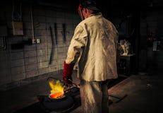 Reifer Mann überprüft Hitze des Tiegels auf Bleibronze gießen Stockbild