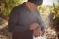 Reifer Mann auf Autumn Run Checking Activity Tracker stockfotos