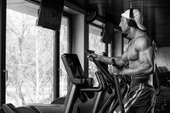 Reifer Mann, der Aerobic elliptischen Walker In Gym tut Lizenzfreies Stockfoto