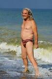 Reifer Mann, der auf dem Seestrand ein Sonnenbad nimmt Lizenzfreie Stockfotografie