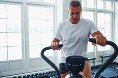 Reifer Mann, der auf einem Standrad an der Turnhalle exercing ist stockbild