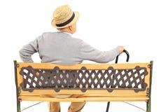 Reifer Mann, der auf einer Holzbank sitzt Lizenzfreie Stockfotos