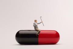 Reifer Mann, der auf einer riesigen Pille sitzt Lizenzfreie Stockfotografie
