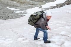Reifer Mann, der auf glatter steiler Steigung des Berges auf Schneefeld klettert Lizenzfreies Stockbild