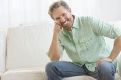 Reifer Mann, der auf Sofa In Living Room sich entspannt lizenzfreie stockfotos