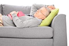 Reifer Mann, der auf Sofa schläft und ein Buch hält Stockbild