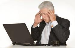 Reifer Mann, der am Computer sitzt Lizenzfreie Stockbilder