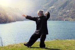 Reifer Mann, der draußen Tai Chi-Disziplin übt stockfoto