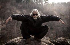 Reifer Mann, der draußen Tai Chi-Disziplin übt stockbild