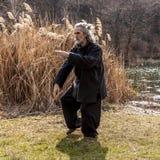 Reifer Mann, der draußen Tai Chi-Disziplin übt stockfotos