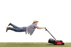 Reifer Mann, der durch einen Rasenmäher gezogen wird Stockfoto