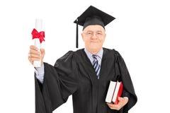 Reifer Mann, der ein Collegediplom hält Stockbild