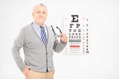 Reifer Mann, der ein Paar Gläser vor einer Sehtafel hält Lizenzfreies Stockfoto