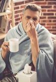 Reifer Mann, der eine Kälte hat Stockbild