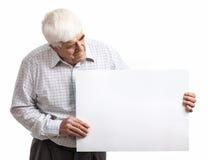 Reifer Mann, der eine leere Anschlagtafel über Weiß hält Lizenzfreies Stockfoto