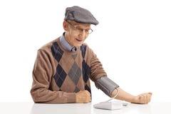 Reifer Mann, der an einem Tisch sitzt und seinen Blutdruck misst lizenzfreie stockfotos