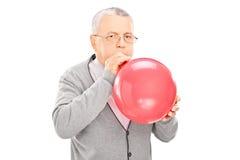 Reifer Mann, der einen Ballon explodiert Stockfoto