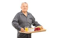 Reifer Mann, der einen Behälter mit Getreide hält Stockfotografie
