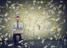 Reifer Mann, der einen Laptop errichtet on-line-GeschäftsDollarscheine und die Glühlampen unten fallen verwendet stockfotos