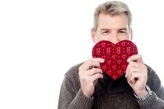 Reifer Mann, der geformte Geschenkbox des Herzens hält Stockfoto