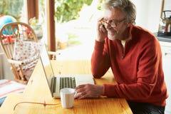 Reifer Mann, der Handy und Laptop verwendet Stockbild