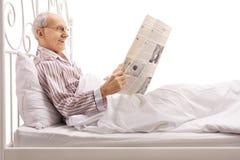 Reifer Mann, der im Bett liegt und eine Zeitung liest Stockbild