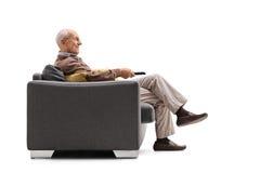 Reifer Mann, der im Couch und aufpassendem Fernsehen sitzt Stockfoto