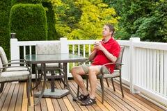Reifer Mann, der im Stuhl auf Patio im Freien mit Tasse Kaffee stillsteht Stockfotografie