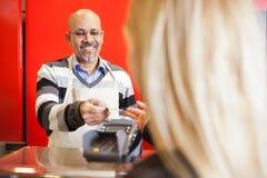 Reifer Mann, der Kreditkarte von der jungen Frau annimmt Lizenzfreie Stockfotos