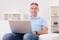 Reifer Mann, der Laptop verwendet Stockbild