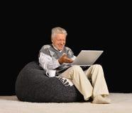 Reifer Mann, der Laptop verwendet Lizenzfreies Stockbild