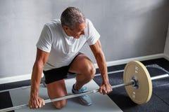 Reifer Mann, der mit Gewichten an der Turnhalle trainiert stockfoto