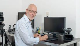 Reifer Mann, der mit seinem Computer arbeitet stockbild