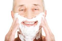 Reifer Mann, der Schaum rasierend zutrifft Stockfoto