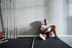 Reifer Mann, der seine Mitteilungen nach einem Fitnessstudiotraining überprüft stockbilder