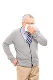 Reifer Mann, der seine Nase mit durchbrennt Lizenzfreie Stockfotografie