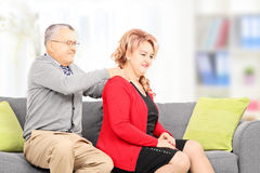 Reifer Mann, der seiner Frau Massage gesetzt auf Couch gibt Stockbilder