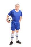 Reifer Mann in der Sportkleidung, die einen Fußball hält Lizenzfreie Stockbilder